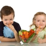 Happy kids with a bowl of vegetables, smiling and eating carrot - isolated
